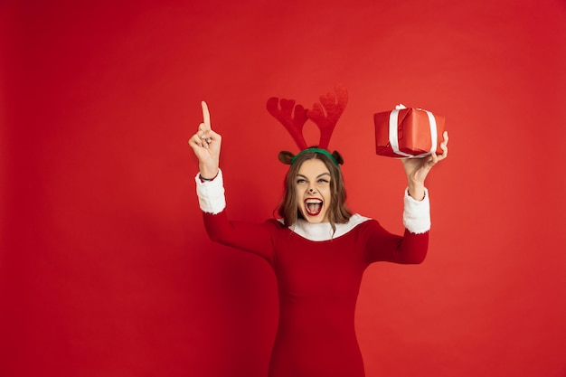 Beautiful woman like christmas deer isolated on red surface concept of  new years winter mood holidays