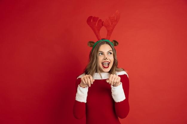 Bella donna come cervo di natale isolato sul concetto di superficie rossa delle vacanze invernali dell'umore di nuovi anni