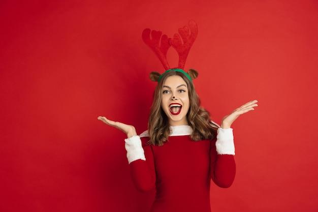 Beautiful woman like christmas deer isolated on red wall