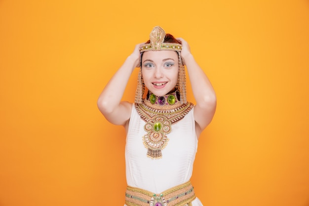 Bella donna come cleopatra in antico costume egiziano felice ed eccitata che si tiene per mano sulla testa sull'arancia