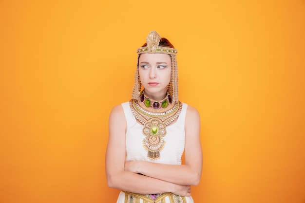 Beautiful woman like cleopatra in ancient egyptian costume looking aside offended being angry at someone with arms crossed on orange