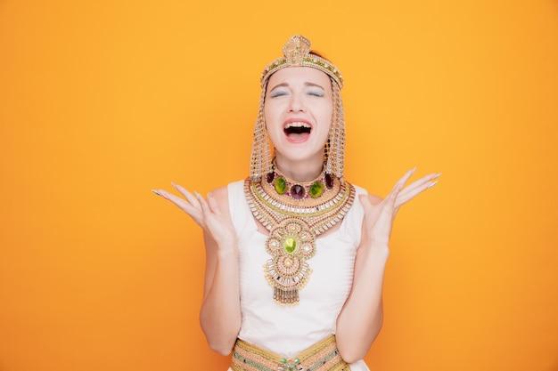 고대 이집트 의상을 입은 클레오파트라 같은 아름다운 여성이 화를 내고 좌절하며 주황색에 공격적인 표정으로 팔을 들고 소리를 질렀다