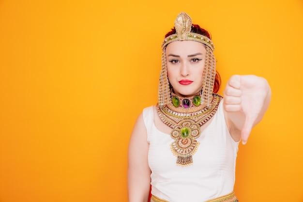 古代エジプトの衣装を着たクレオパトラのような美しい女性は、オレンジ色に親指を下に見せることに不満を持っています