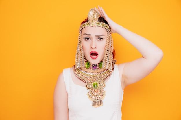 古代エジプトの衣装を着たクレオパトラのような美しい女性は、オレンジ色の間違いのために彼女の頭に手をつないで混乱し、驚いた 無料写真