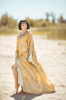 砂漠の屋外でエジプトの女王クレオパトラのような美しい女性