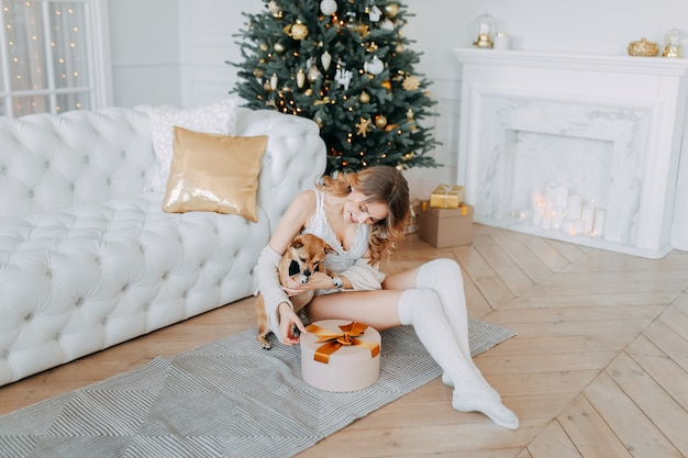 Beautiful woman in lingerie and leggings decorates the christmas tree near the fireplace at home