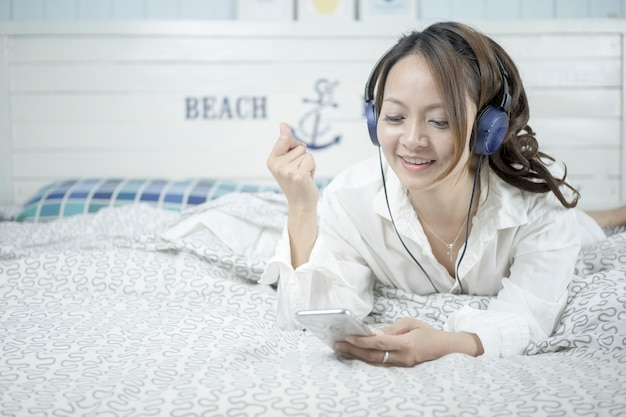 Beautiful woman listening music in headphones on her bed.