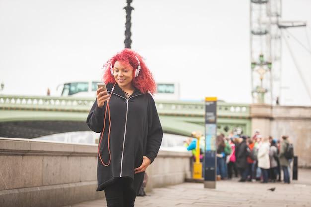 Красивая женщина слушает музыку в лондоне