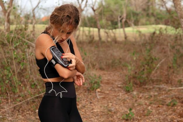 Bella donna che ascolta musica nel parco