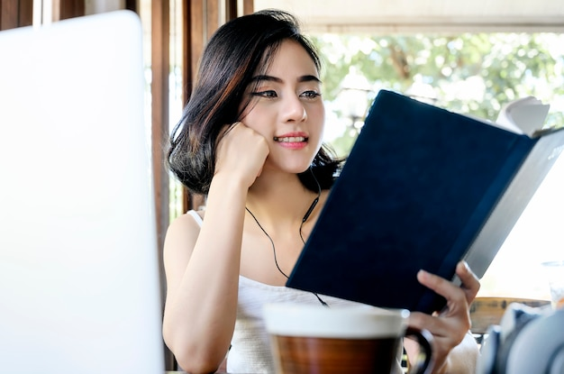 Beautiful woman listening music and reading book while take a break with happiness at cafe.