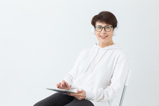 白い壁にタブレットを保持している大きなヘッドフォンで音楽を聴いて美しい女性