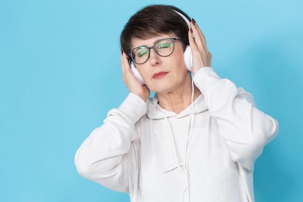 青い壁に大きなヘッドフォンで音楽を聴いている美しい女性