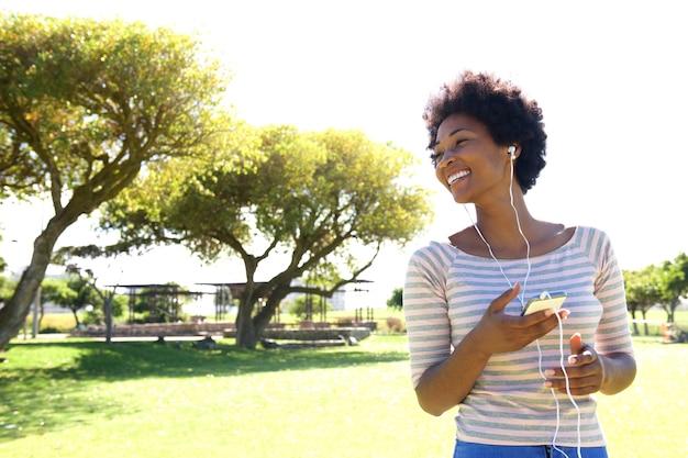 Красивая женщина, слушать музыку на смарт-телефон за пределами