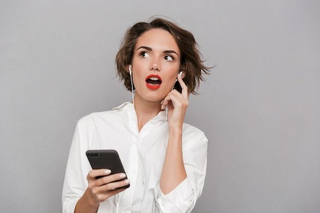 灰色の壁に隔離されたイヤホンを介してスマートフォンで音楽を聴く美しい女性