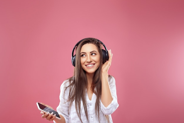Красивая женщина слушает музыку с помощью беспроводных наушников
