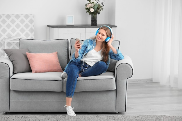 Красивая женщина слушает музыку, отдыхая на диване у себя дома