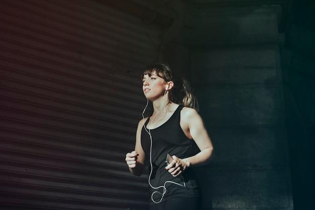 Красивая женщина слушает музыку во время бега