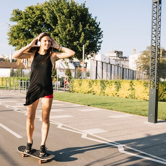 Beautiful woman listening to music while skateboarding on street