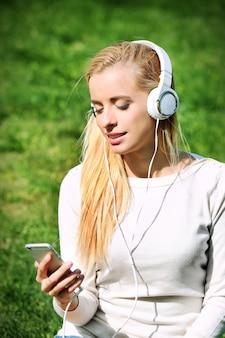 야외에서 헤드폰으로 음악을 듣고 아름 다운 여자