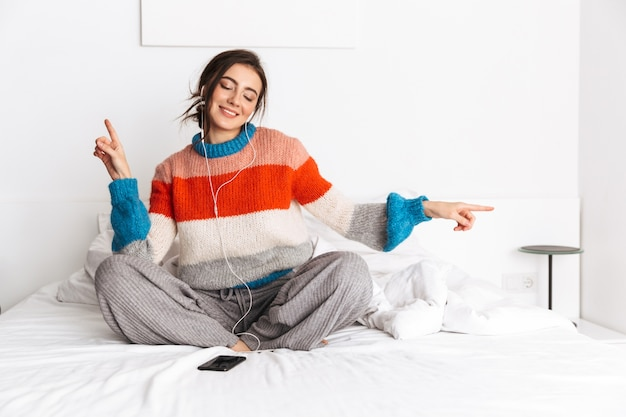 집에서 침대에 앉아있는 동안 스마트 폰과 이어폰으로 음악을 듣고 아름다운 여자