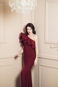 Beautiful woman in a long dark evening dress with a beautiful hairstyle and makeup