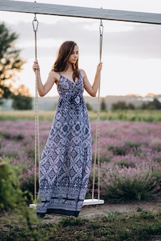 Beautiful woman in a long dress on a swing in a lavender field at sunset.