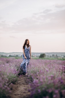 Beautiful woman in a long dress walking in a lavender field at sunset.