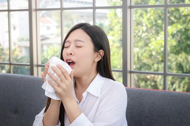 아름 다운 여자 긴 머리 아시아 아픈 기침 또는 재채기 휴지로 입과 코를 가리십시오. 건강 치료의 개념 바이러스의 전파 방지