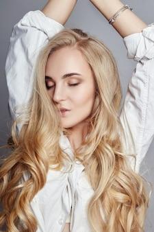 ウルトラブロンドのナチュラルメイクで美しい女性の長い髪の色。ビューティーサロンで行われるスタイリッシュなヘアスタイルのカール。ファッションブロンドの女の子