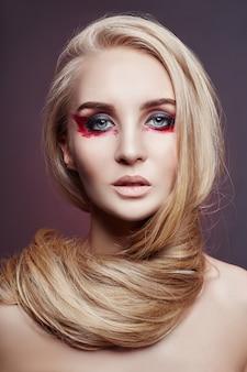 ウルトラブロンドのナチュラルメイクで美しい女性の長い髪の色。ビューティーサロンで行われるスタイリッシュなヘアスタイルのカール。ファッション金髪女性