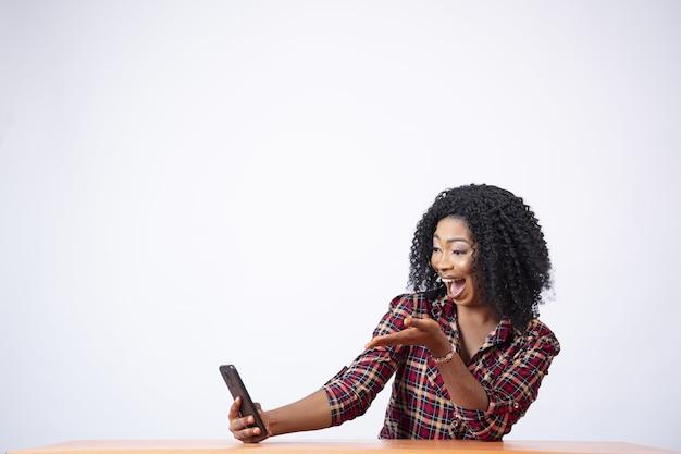 彼女の電話を見て驚いて興奮している美しい女性