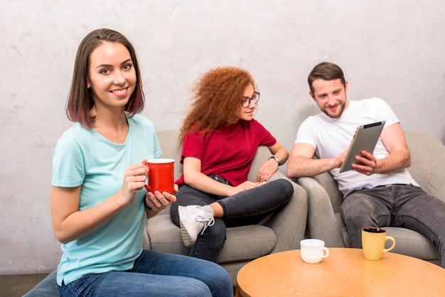 Bella donna che guarda l'obbiettivo che tiene tazza di caffè che si siede con gli amici guardando la tavoletta digitale