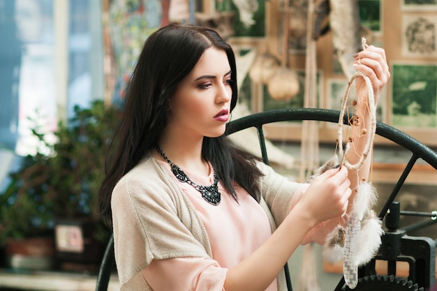 Beautiful woman looking at created dreamcatcher