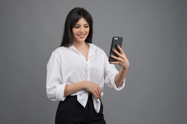 Beautiful woman looking at her phone isolated over grey