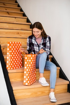 Beautiful woman looking inside bags sitting on stairs