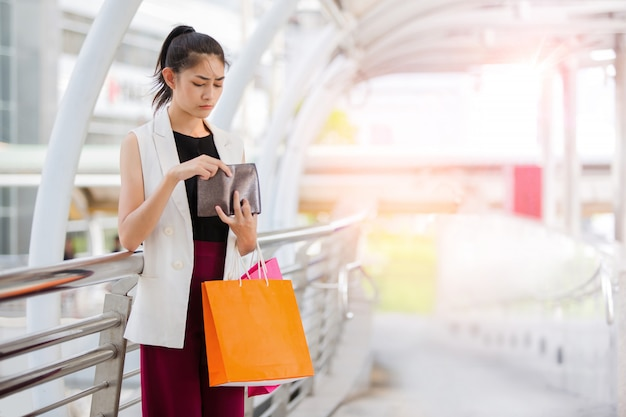 Beautiful woman looking in open wallet with shocked expression while holding color shopping bags