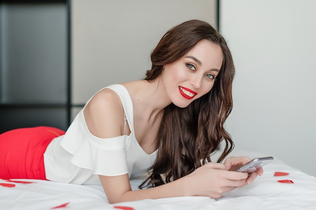 Beautiful woman looking at phone screen in bed with heart shaped confetti at home