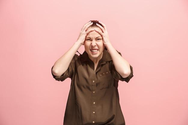 ピンクの壁に分離されて驚いて戸惑う美しい女性