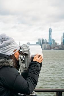 Красивая женщина смотрит в телескоп в нью-йорке в пасмурный день - вертикальное изображение