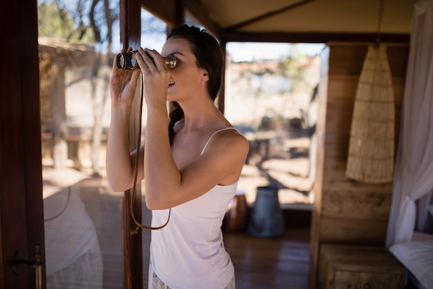 Beautiful woman looking through binoculars from window