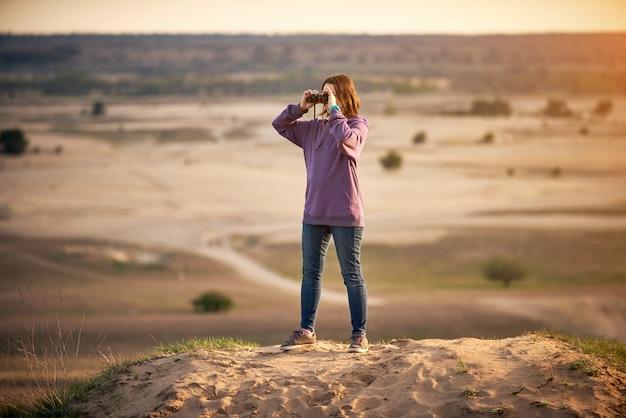 Beautiful woman looking through binoculars outdoors at sunset