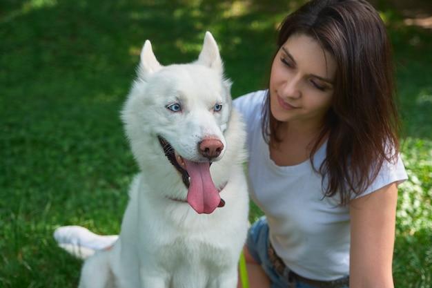 Красивая женщина, глядя на ее очаровательны белая собака с голубыми глазами