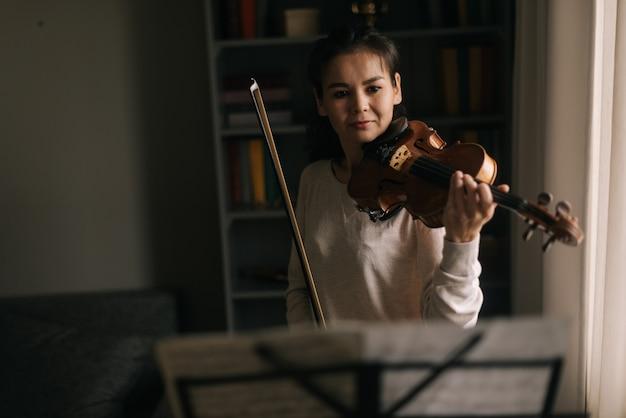 Красивая женщина смотрит на партитуру, играя на скрипке. девушка занимается игрой на музыкальном инструменте дома.