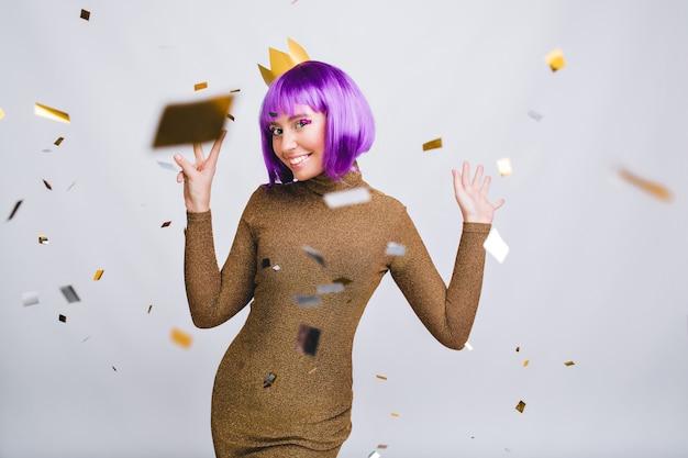 Bella donna in abito di lusso divertendosi in tinsel volante. indossa un taglio di capelli viola, corona d'oro, sorridendo
