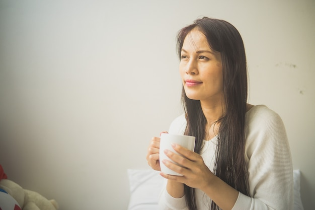 Beautiful woman lying in bed with a cup of coffee