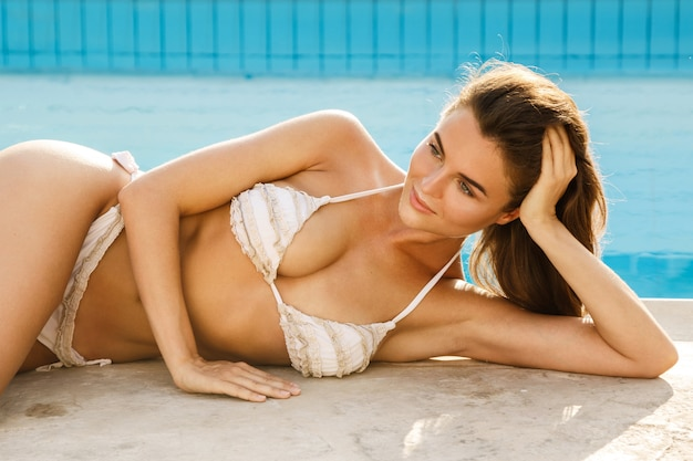 Beautiful woman lying beside a swimming pool