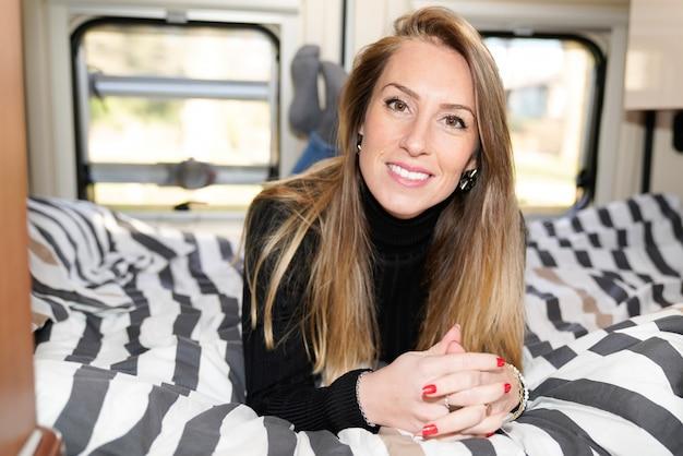 Beautiful woman lying in a camper van rv in summer day vanlife motor campervan home