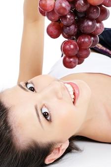 床に横になって、ブドウの束を保持している美しい女性