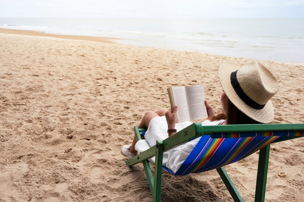 A beautiful woman lying down and reading book on the beach chair with feeling relaxed