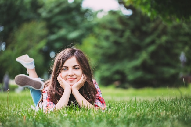 Beautiful woman lying on green grass